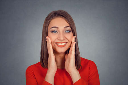 Closeup portrait of happy cute young woman in red dress looking excited surprised in full disbelief hands on cheeks isolated on gray grey studio wall background. Positive human emotion face expression