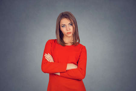 Grumpy wife. Closeup portrait of angry young woman puffing cheeks. Business lady in red dress, bob hairstyle. Isolated on gray grey studio wall Background. Negative face expressions, human emotions.