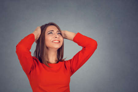 Closeup portrait young angry unhappy stressed woman covering her ears looking up stop making loud noise it's giving me headache isolated grey wall background. Negative emotion face expression feeling