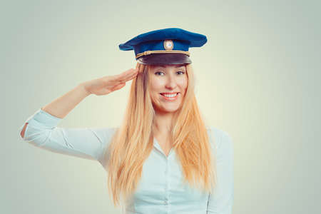 Charming blond woman in blue service cap giving salute at camera and smiling