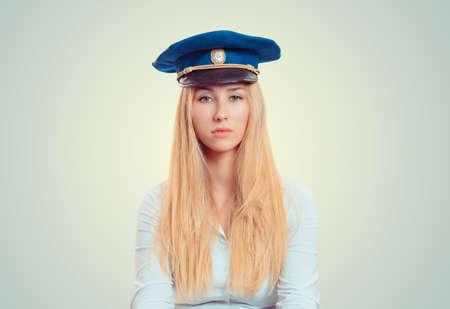 Young blond woman wearing blue forage cap and looking unemotionally at camera