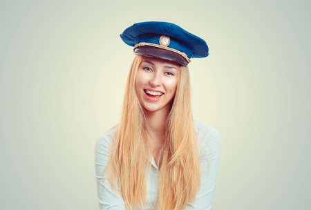 Charming young blond woman in white shirt and blue forage cap smiling at camera 版權商用圖片