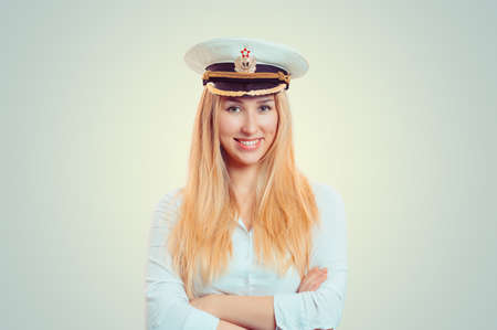 Pretty blond woman in white shirt and white navy service cap smiling at camera 版權商用圖片