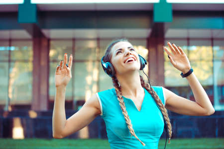 Content sportive woman in headphones dancing cheerfully on street listening to music