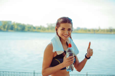 Modern fit woman in sportswear standing with towel and bottle on seafront showing thumb up 版權商用圖片