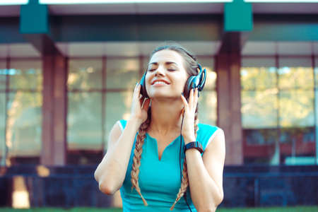 Training young brunette listening to music with headphones and enjoying it while standing outdoors 版權商用圖片