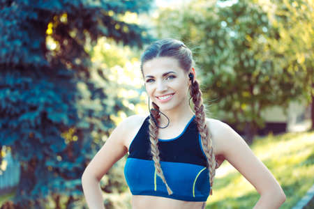 Young fit athletic woman in top and headphones standing in park and looking at camera 版權商用圖片