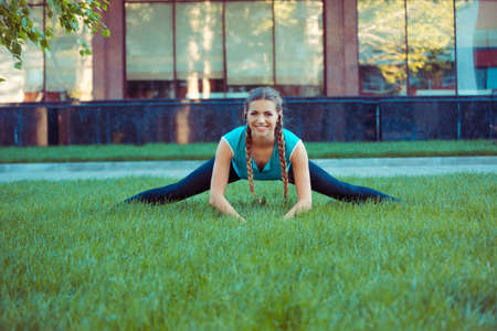 Pretty young brunette in sportswear stretching legs on green meadow standing in splits and smiling at camera