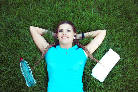 From above of young fit sportswoman lying on green lawn with bottle of water and towel in relaxation