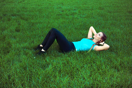 Slim sportive woman training abs on green lawn in park