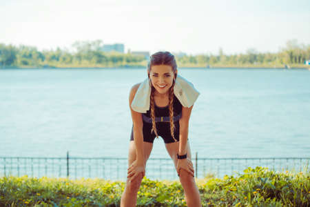 Slim young athletic woman bending on knees and smiling at camera on city waterfront