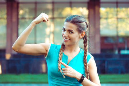 Charming fit sportswoman showing bicep at camera with smile on urban background