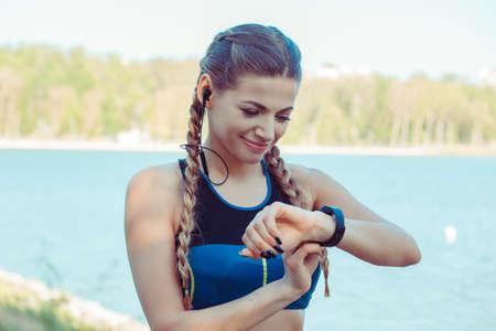 Modern slim sportive woman in headphones using smart watch while standing outdoors 版權商用圖片