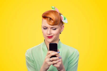 Portrait upset skeptical unhappy serious woman looking at texting on phone displeased with conversation isolated yellow background retro vintage 50's style. Negative human emotion face expression
