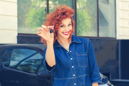 Portrait happy, smiling, young attractive woman, buyer near her new car showing giving keys isolated outside dealer dealership lot office. Personal transportation auto purchase concept