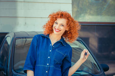 Woman showing her new car key smiling happy posing in the parking lot outdoors, outside in summer day in city apartment building on background. Positive human emotions face expression feeling