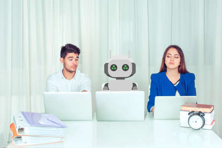 Young man and woman corporate employees with laptops looking jealous about new innovative robot colleague working sitting at table, being envy about his much effective work being worried to loose jobs.