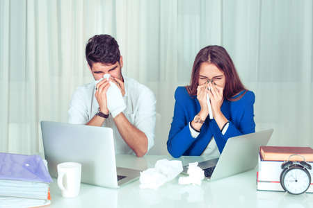 Young man and woman couple colleagues blowing nose with tissues while working sitting together at table in office living room at home. Influenza virus allergia, flu from air conditioner concept.