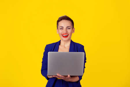 Portrait young happy business woman with short hair holding computer laptop looking at camera smiling laughing excited isolated yellow background. Positive face expression emotion. Technology concept.