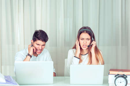 Angry customer service representatives. Young frustrated man and woman speaking with talking to customer, clients and screaming with stress and anger working in support call service center in office.