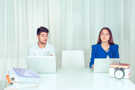 Young modern man and woman with computers at table looking envy and skeptical on empty vacant place