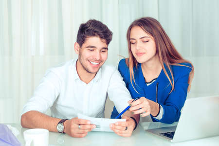 Young smart woman pointing with pen on paper showing information to young male man colleague working in team. Happy couple colleagues sharing work sitting at table in office living room at home.