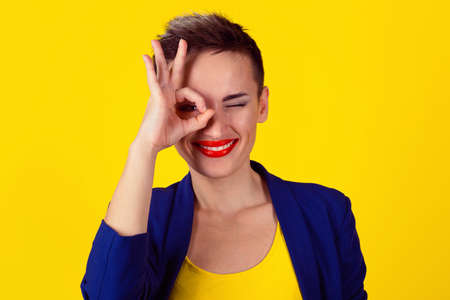 Woman with her fingers over one eye, ok sign hand gesture isolated on yellow background. Model in yellow shirt and blue suit. Satanic 666, Illuminati symbol and sign of the mark of the beast on eye.