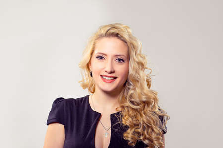 Portrait of wonderful woman with blond curly hair wearing black outfit and smiling at camera