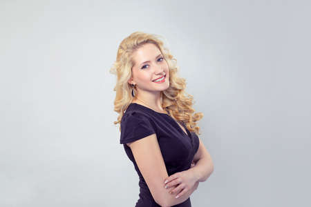 Side view of young smiling blonde in black dress standing on gray background looking at camera