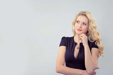 Charming young blond woman in black dress dreaming and looking away on gray background