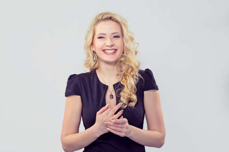 Amazing blond woman in elegant black dress laughing excitedly at camera