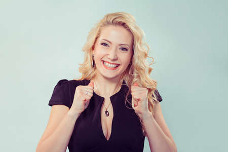 Pretty blond woman in black dress holding hands in supporting gesture and smiling at camera