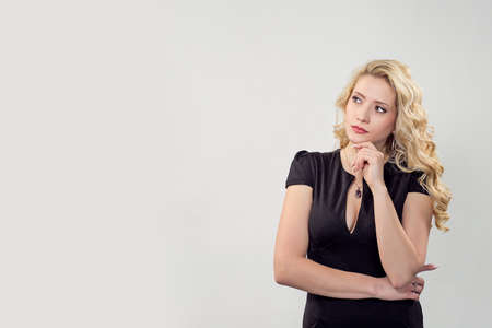 Elegant blond woman touching chin while looking away in contemplations on gray backdrop