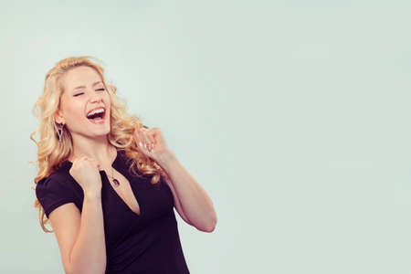 Modern blond woman holding fists in excitement of success keeping eyes closed