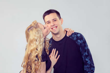 Blond woman kissing handsome young man in cheek standing on gray background