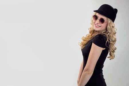 Side view of trendy blond woman in black t-shirt and cap wearing sunglasses and posing flirty