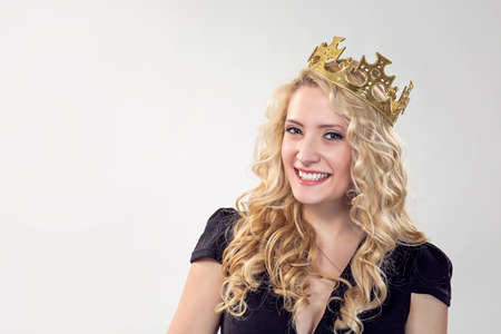 Adorable blond woman wearing golden crown and smiling happily at camera