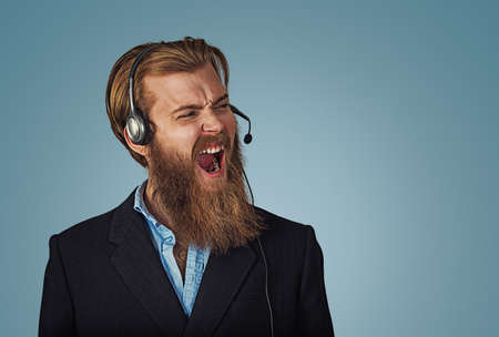 Young adult hipster man with headset working as operator annoyed, frustrated shouting with anger, crazy and yelling, angry customer service representative concept on blue Background. Negative face Banco de Imagens