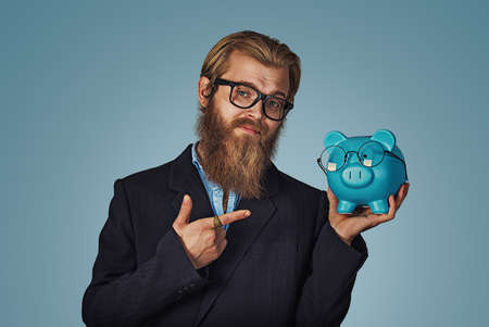Close-up Of Bearded Hipster Businessman Holding blue Piggybank With Eyeglasses pointing at it with hand index finger Isolated on blue Background. Positive face expression, human emotion, body language