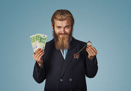 Time is money. Handsome cheerful bearded hipster man smiling with cash and pocket watch. Funny guy is a lucky winner holding a pile of money and a watch he is happy to win the jackpot isolated on blue