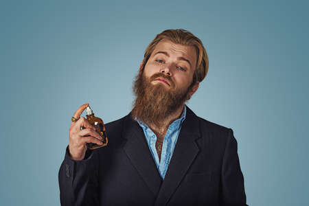 Rich hipster bearded man using expensive perfume eau de cologne perfume isolated on blue background. Positive face expression, human emotion, body language, reaction, attitude. Studio Horizontal shot.