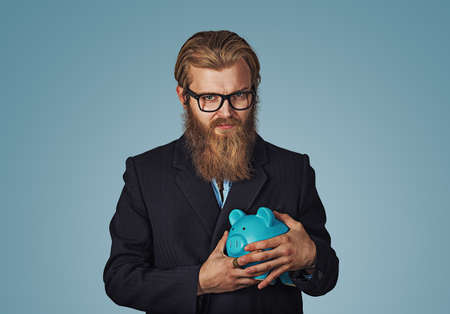 Young greedy stingy Bearded hipster businessman man holding piggy bank Isolated on blue studio wall Background. Negative face expression human emotion body language reaction attitude. Horizontal Banco de Imagens