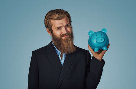 Portrait of a smiling Bearded business man holding piggy bank money box Isolated on blue studio wall Background. Positive face expression human emotion body language reaction attitude. Horizontal Banco de Imagens