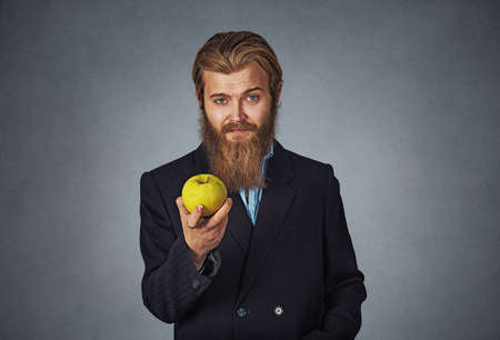 Diet concept. Businessman Bearded hipster business man showing giving holding a green apple in his hand Isolated on gray grey studio wall Background. Positive face expression, emotion, body language.