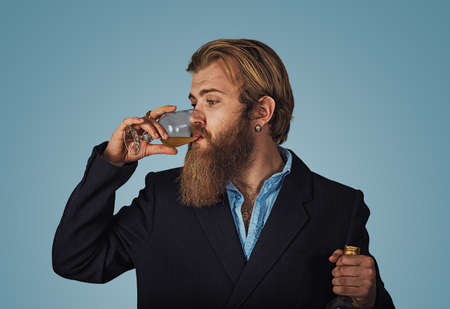 Handsome bearded well-dressed man in jacket holding tasting drinking glass of beverage whiskey alcohol isolated on grey gray studio background wall. drinks, relax, leisure and people concept.