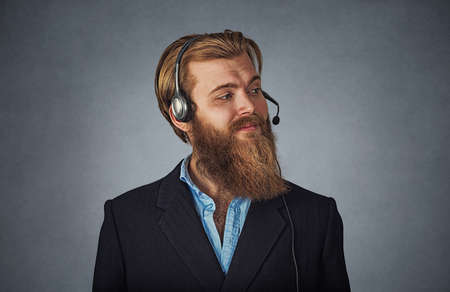 Side profile view portrait of confident cheerful customer service representative smiling. Bearded hipster business man in headset Isolated on gray grey studio wall Background. Positive face expression Banco de Imagens