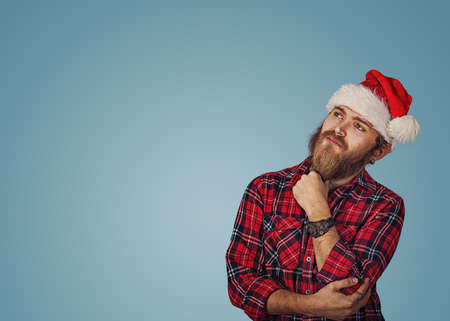 Bearded handsome hipster young man in Christmas hat looking up posing in studio thinking of gift ideas isolated on blue studio wall background with copy space. Positive face expression emotion feeling