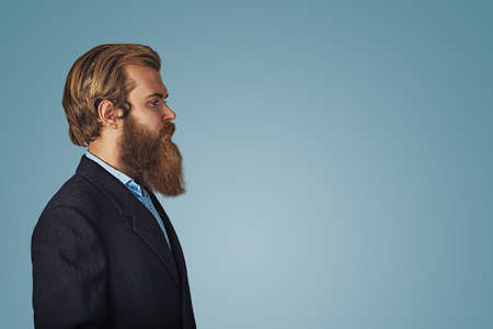 Side view portrait of serious fashionable bearded hipster handsome man in black suit and blue shirt Isolated on blue Background. Negative face expression, human emotion body language reaction attitude
