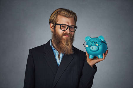 Closeup portrait head shot young serious smiling happy hipster businessman holding Piggy bank both wearing glasses isolated on gray studio wall background. Save money, savings on eyeglasses concept