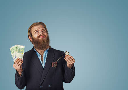 Portrait of an adult Bearded hipster businessman cheerful positive man pumping fists standing isolated over blue studio wall background looking up holding money and pocket watch clock Isolated on blue Banco de Imagens